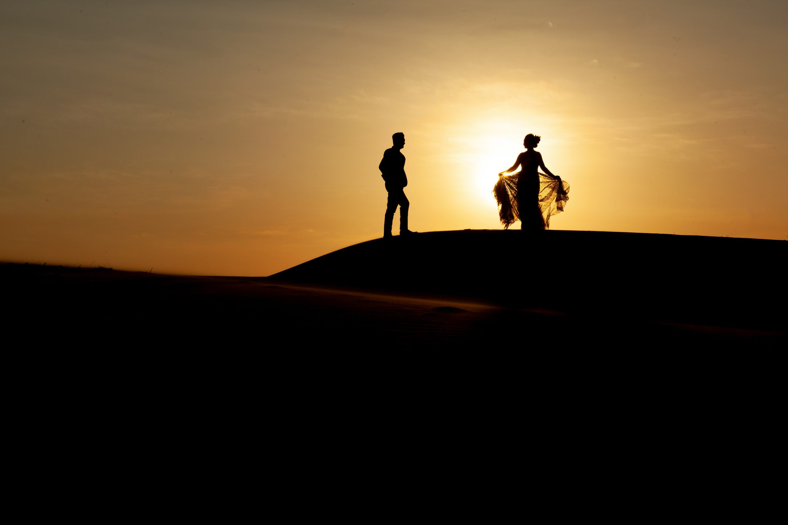 silhouette-of-two-people-walking-on-sand-during-sunset-3998369