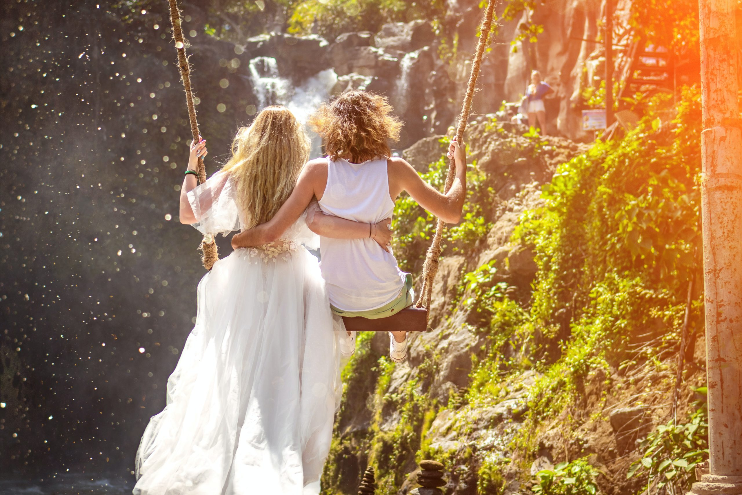 woman-and-woman-riding-wooden-swing-in-front-of-rock-1459583